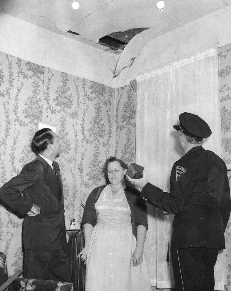 The Mayor Ed J. Howard, Mrs Hodges and the chief of police W.D. Ashcraft observing Ann Elizabeth Hodges's ceiling in Sylacauga, Alabama, in 1954. Mrs Hodges had just been hit by a meteorite that fell on her hip while she was taking a nap